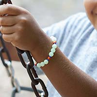 Young boy on swing wearing beaded medical ID bracelet with glow-in-the-dark beads.