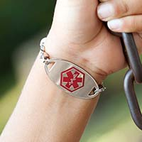Little boy on swing showing medical alert tag on medical ID bracelet with red caduceus facing forward.