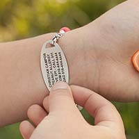 Girl flipping over medical ID tag to show the medical details custom laser engraved on back of tag.