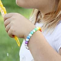 Young girl blowing bubbles in field, wearing medical ID bracelet with rainbow colored silicone beads.