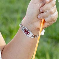 Little girl holding bubble blowing wand, showing medical alert tag on colorful medical ID bracelet with red symbol facing forward.