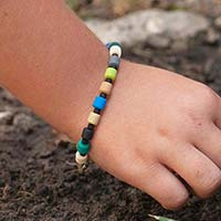 Young boy wearing earth tone beaded medical ID bracelet.