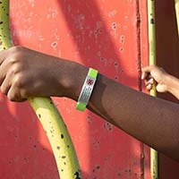 Boy climbing on train car at park wearing green silicone bracelet with silver medical ID tag with red symbol and custom engraving.