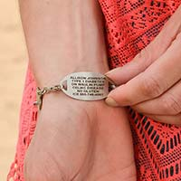 Woman wearing and showing engraving on the Oval Border Medical ID Tag, red caduceus, worn on the Sea Life Medical ID Bracelet