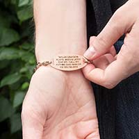 Woman shows engraving on a Rose Gold Tone Oval Med ID Tag on Forever and Always Medical ID with infinity-symbol-shaped links