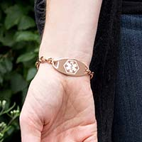Woman wearing a Rose Gold Tone Oval Med ID Tag on a Forever and Always Medical ID with stainless infinity-symbol-shaped links