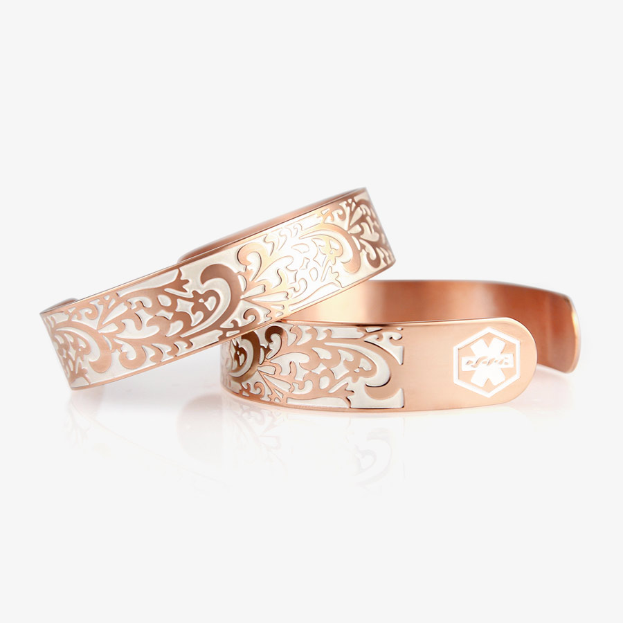 Two identical rose gold tone cuff bracelets with swirl filigree pattern and pearl white medical symbols