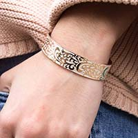 Woman wearing the plated stainless Rose Gold Tone Filigree Medical ID Cuff with intricate scroll design, pearlescent inlay