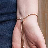 Woman showing the back of the stainless slip-on SmartFit Medical ID Bracelet in Rose Gold Tone with SmartBead slide to adjust