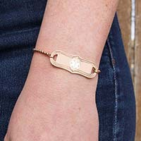 Woman wearing the rose tone stainless SmartFit Medical ID Bracelet in Rose Gold Tone with the rose La Petite medical ID tag