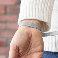 Woman showing the open mesh chain and slip-through magnetic closure on the silver-tone stainless Urban Medical Alert bracelet