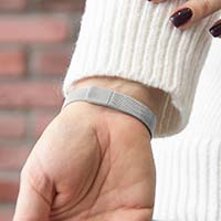 Woman showing the mesh chain with slip-through magnetic closure on the silver-tone stainless Urban Medical Alert bracelet