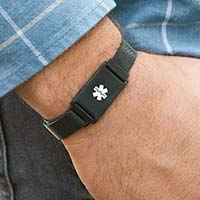 Man wearing Urban Medical Alert in Black bracelet with black mesh chain, magnetic closure, affixed ID tag with white caduceus