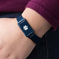 Girl wearing blue tone stainless steel medical alert band with white medical symbol
