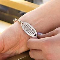 Woman showing custom laser engraving medical ID tag