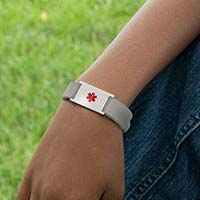 Boy wearing grey silicone medical alert band with stainless steel medical ID tag