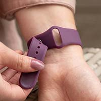 Woman opens pin-tuck watch band closure on grape colored silicone medical alert bracelet