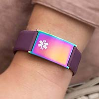 Woman wearing grape silicone medical ID bracelet with oversized Metro ID tag in multi-colored magic finish with white caduceus.
