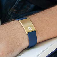 Man reading book wearing navy silicone medical ID bracelet with oversized Metro ID tag in brushed gold.