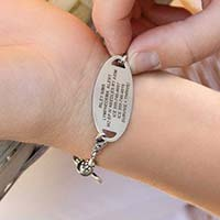 Sample engraved text on back of medical ID tag shown on wrist