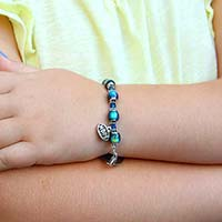 Young girl with arms crossed wearing fun mood bead medical ID bracelet