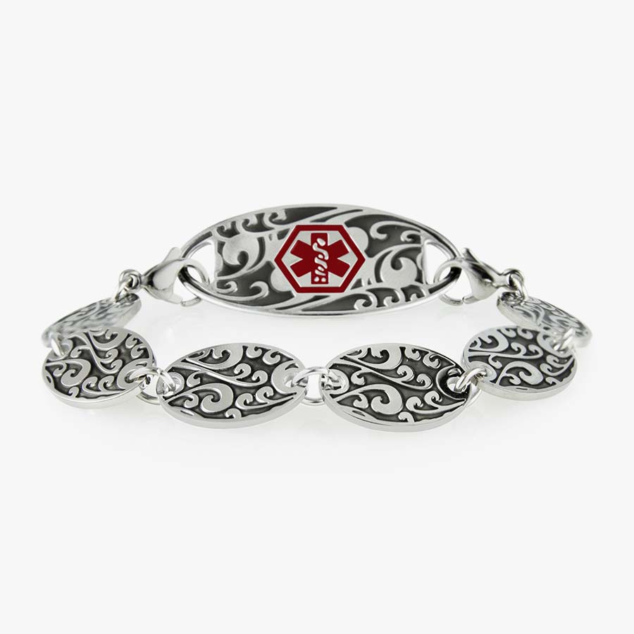 Decorative chain bracelet with circular patterned links and intricate medical alert tag