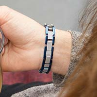 Woman showing clasp of blue and silver tone medical alert bracelet with watch style links