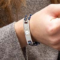 Woman wearing blue and silver linked medical ID bracelet with white medical symbol