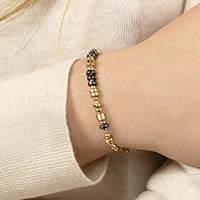 Woman wearing gold and black beaded medical alert bracelet