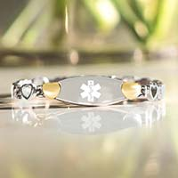 Low angle image of silver and gold linked medical alert bracelet in front of vase of flowers