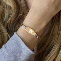 Woman showing gold and silver linked style medical ID bracelet with heart accents