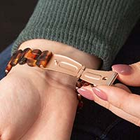 Woman in white sweater holding coffee mug displays tortoiseshell resin and rose gold medical ID bracelet with white caduceus symbol.