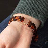 Woman wearing green sweater closing rose gold clasp on medical ID bracelet with tortoiseshell resin band.