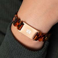 Woman wearing green sweater with back of wrist turned to display closed rose gold clasp on resin medical ID bracelet.