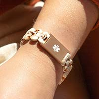 Woman wearing rose gold and cream medical ID bracelet with white medical caduceus symbol.