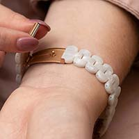 Woman wearing pink blouse prepares to close the open rose gold clasp on medical ID bracelet with pearl resin band.