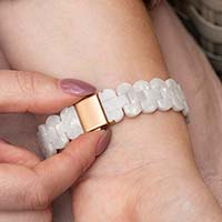 Woman wearing pink blouse pushes release buttons to open rose gold clasp on medical ID bracelet with pearl resin band.