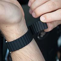 Man adjusts clasp-free magnetic band on black silicone medical ID bracelet.
