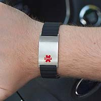 Man opening car door wearing black magnetic medical ID bracelet with silver tag and red medical symbol.