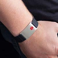 Man wearing blue jeans and black shirt displays magnetic silicone bracelet with black band, silver tag, and red caduceus on his wrist.