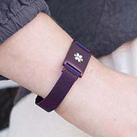 Woman wearing plum plated stainless Urban Medical Alert bracelet with mesh chain and affixed ID tag with white caduceus.