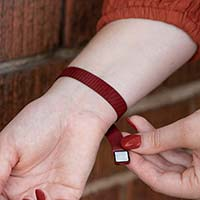 Woman opening mesh chain band with magnetic closure on crimson red stainless Urban Medical Alert bracelet.