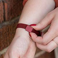 Woman closing mesh chain band with magnetic closure on crimson red stainless Urban Medical Alert bracelet.