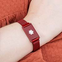 Woman wearing crimson red stainless Urban Medical Alert bracelet with mesh chain and affixed ID tag with white caduceus.