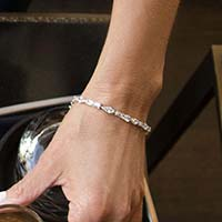 Woman wearing Cantata Medical ID Bracelet in Sterling silver with 3 shapes cubic zirconia and La Petite tag, white caduceus