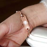Woman showing decorative rose gold medical alert tag with curved edge