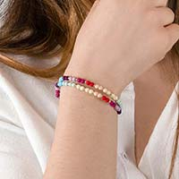 Woman wearing multicolor beaded medical alert bracelet with blue, purple, green, and yellow