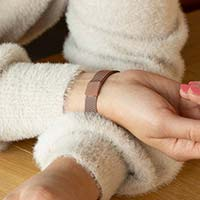 Woman showing magnetic clasp of mauve pink medical alert bracelet