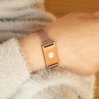 Woman showing medical ID bracelet with french pink finish and white medical symbol
