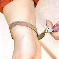 Woman opening mesh chain band with magnetic closure on brushed sandstone plated stainless Urban Medical Alert bracelet.
